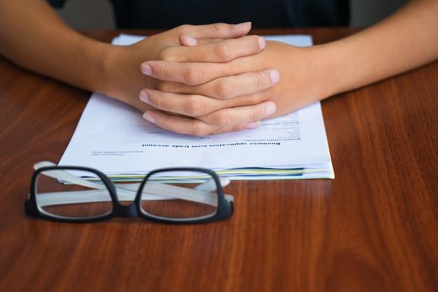 Close-of mani femminili giunte sui documenti