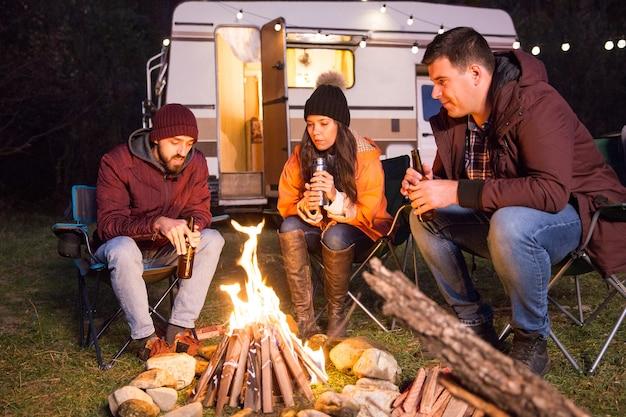Amici intimi seduti insieme su sedie da campeggio intorno al fuoco da campo in montagna. camper retrò.
