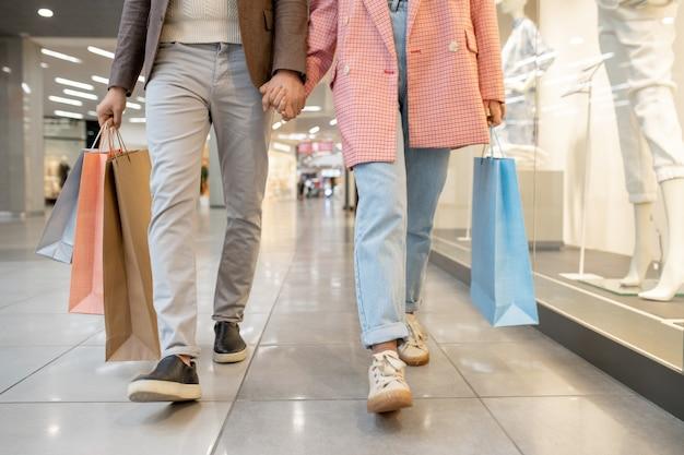 Primo piano di una giovane coppia che si tiene per mano e cammina insieme nel centro commerciale con gli acquisti