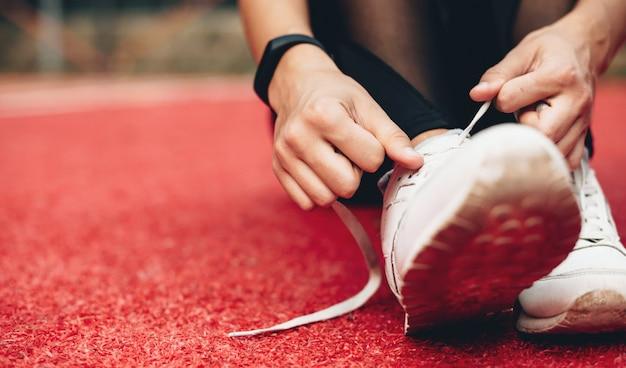 Chiudere la foto di una ragazza caucasica che prepara i suoi stivali per una sessione di jogging in uno stadio sportivo rosso