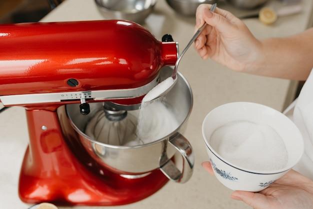 Una foto ravvicinata delle mani di una giovane donna che versa lo zucchero in una ciotola di acciaio inossidabile con gli albumi mentre il robot da cucina rosso lo monta