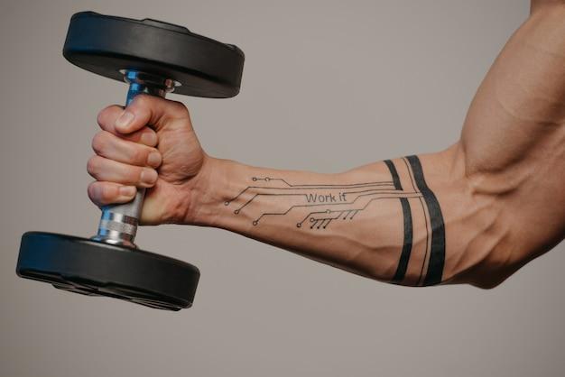 Una foto ravvicinata di un braccio muscoloso che sta facendo riccioli di hummer bicipite con un manubrio