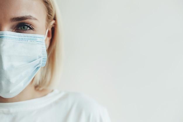 Chiudere la foto di una splendida donna caucasica con i capelli biondi che indossa una maschera medica e una maglietta bianca su una parete dello studio con spazio libero
