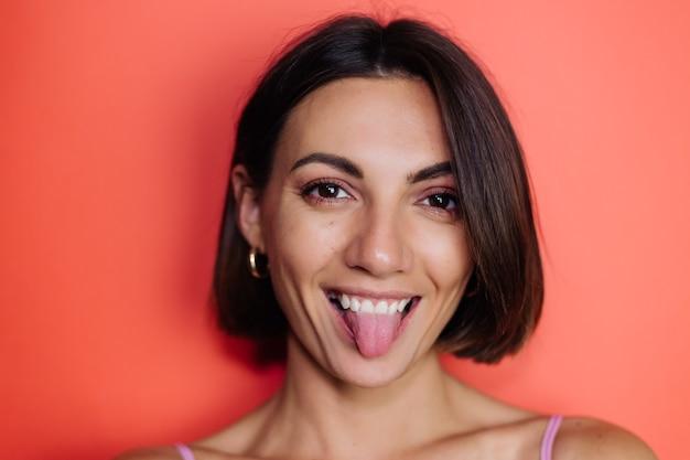 Chiudere il ritratto di donna sul muro rosso giocoso mostra la lingua