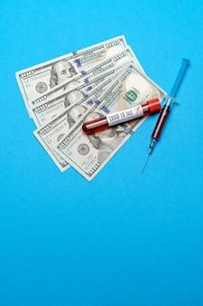 Close up 100 dollari usa e campione di sangue in provetta su sfondo blu