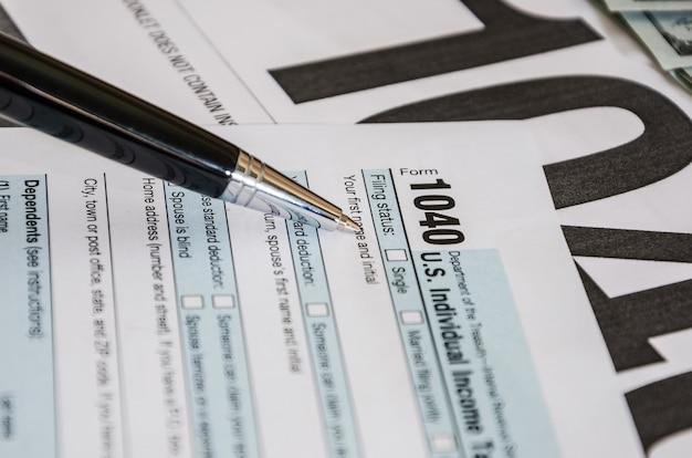 Primo piano di 1040 moduli fiscali e penna