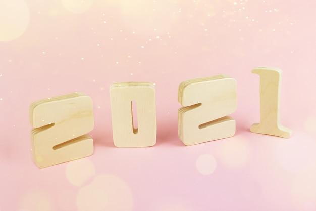 Close-up 2021 calendario in legno su sfondo tavolo rosa con copia spazio per il testo. nuovo anno