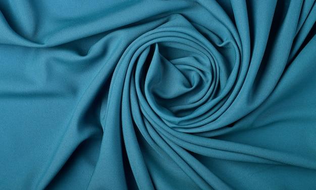 Primo piano astratto sfondo tessile di pieghe piegate blu pastello a forma di spirale di tessuto, vista dall'alto in elevazione, direttamente sopra