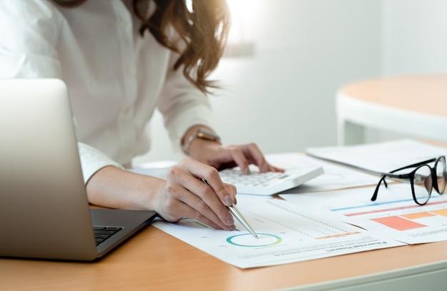 Primo piano contabile che tiene la penna che lavora sulla calcolatrice per calcolare il documento contabile