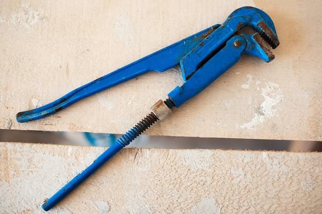 Close-up di chiavi a gas regolabili di colore blu su un tavolo di legno.