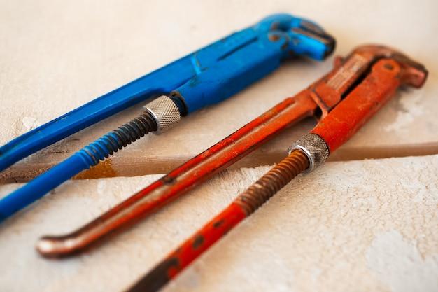 Close-up di chiavi a gas regolabili di colore blu e rosso su un tavolo di legno.