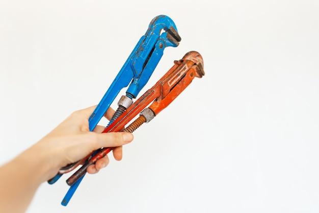 Close-up di chiavi a gas regolabili in mano su sfondo bianco.