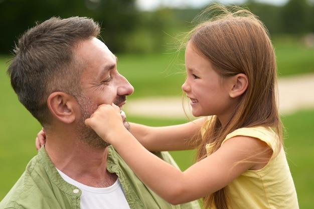 Primo piano di una bambina adorabile che si diverte con il suo amorevole papà che gli tocca il viso mentre è