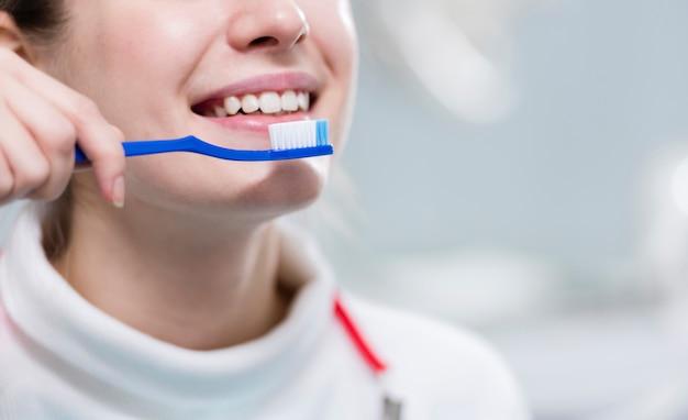 Denti di spazzolatura della donna adulta del primo piano