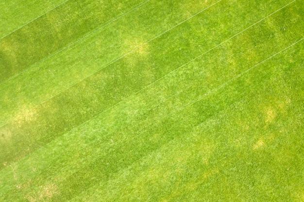 Chiuda sulla vista aerea della superficie dell'erba appena tagliata verde sullo stadio di calcio in estate