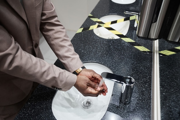Primo piano di un uomo afro-americano che si lava le mani nel bagno pubblico con il lavandino registrato per il distanziamento sociale e le misure di sicurezza covid, spazio di copia
