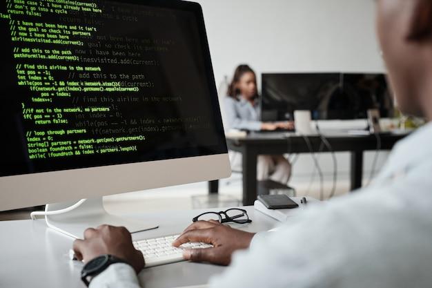 Primo piano di uno sviluppatore di software afroamericano che scrive codice mentre si utilizza il computer in ufficio, spazio di copia