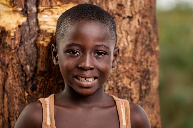 Bambino africano del primo piano che posa vicino all'albero