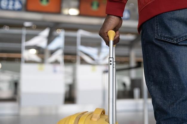 Chiuda sulla mano dell'uomo africano che tocca i bagagli per il check-in al banco in aeroporto
