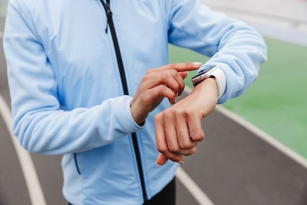 Primo piano di una sportiva africana che utilizza smartwatch allo stadio