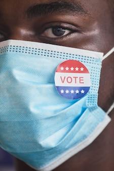 Primo piano dell'elettore africano con il perno con il testo vota sulla sua maschera protettiva