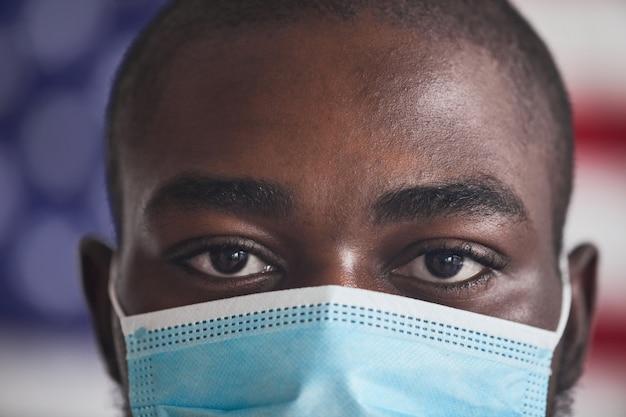 Primo piano del giovane africano che indossa la maschera protettiva durante la pandemia lui