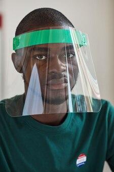 Primo piano del giovane africano che indossa la maschera protettiva