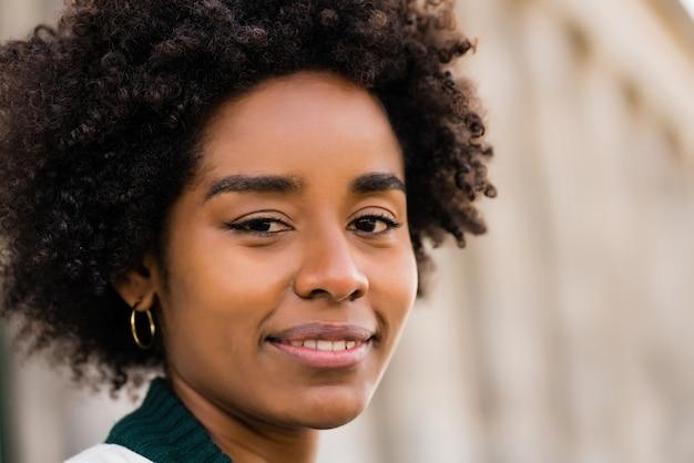 Close up afro business donna sorridente mentre in piedi all'aperto sulla strada. business e concetto urbano.