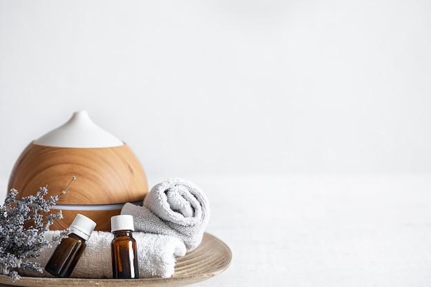 Primo piano di un umidificatore d'aria, oli aromatici naturali, asciugamani e rametti di lavanda