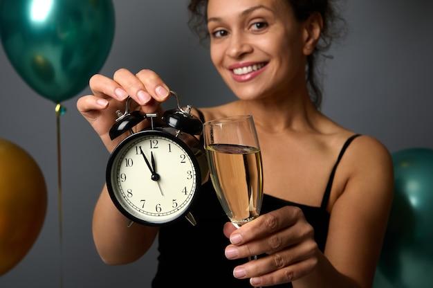 Primo piano di una sveglia e di un flauto di champagne nelle mani di una bella donna sorridente sfocata, isolata su uno sfondo grigio e mongolfiere verdi gonfiate metalliche e dorate, copia spazio per l'annuncio