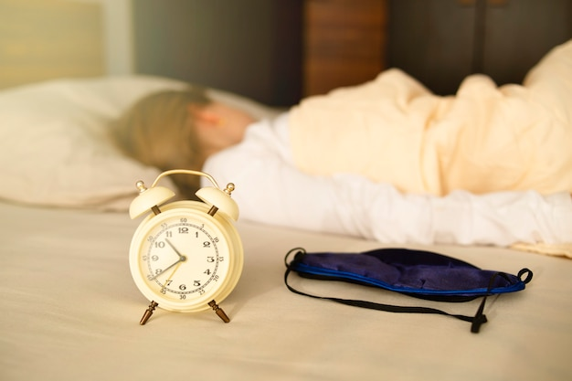 Primo piano di una sveglia e di una maschera per dormire, la ragazza dorme con la schiena girata. dorme a lungo, la mattina tardi.