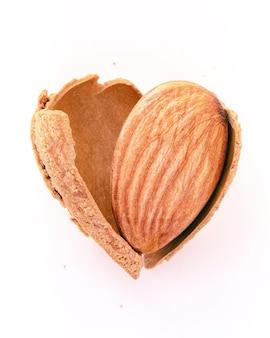 Close up mandorle guscio di noce incrinato a forma di cuore isolato su sfondo bianco. amo il concetto di alimentazione sana.