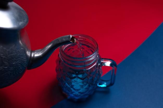 Close-up di teiera in alluminio versando acqua nella tazza di vetro per il succo, su due sfondi di colori rosso e blu.