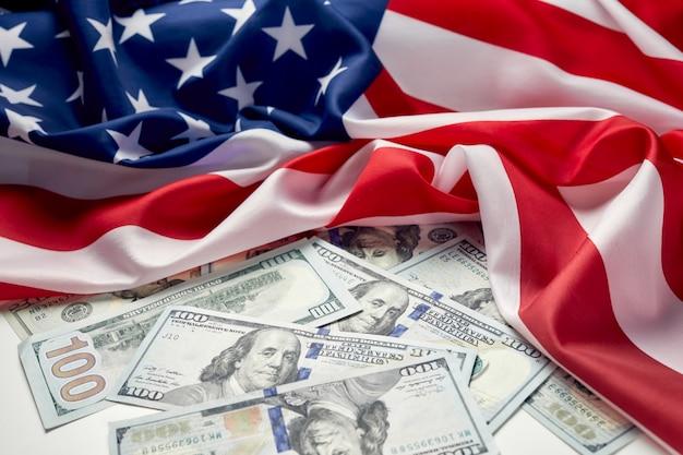 Chiuda in su della bandiera americana e del denaro contante del dollaro