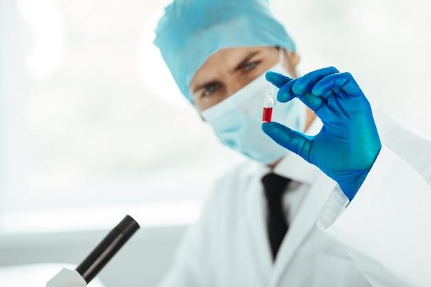 Avvicinamento. fiala con un vaccino nelle mani di uno scienziato. concetto di salute.