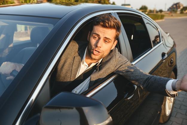 Primo piano di un uomo arrabbiato che guarda fuori dal finestrino della macchina