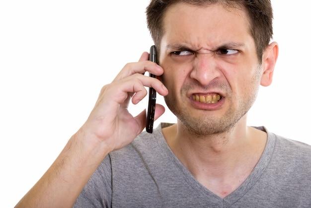 Chiuda in su del giovane arrabbiato che parla sul telefono cellulare