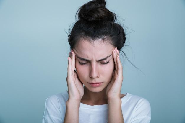 Primo piano di un infastidito giovane donna che indossa t-shirt isolate su sfondo blu, avendo un mal di testa