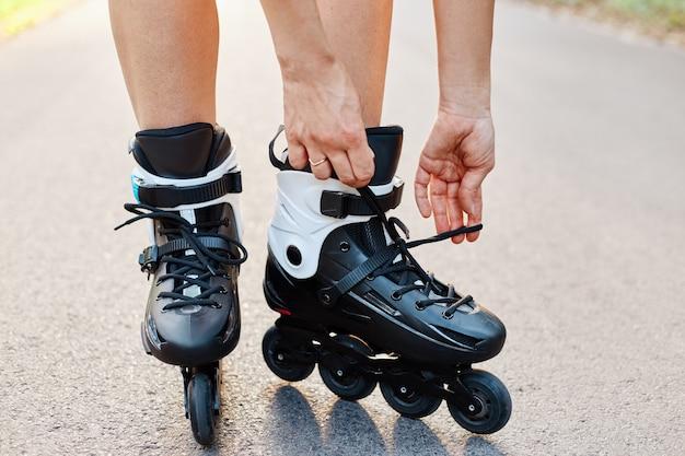 Primo piano delle mani di una donna anonima che fissano i lacci sui pattini durante il pattinaggio, donna sconosciuta sulla strada nel parco estivo, pattinaggio, stile di vita attivo.