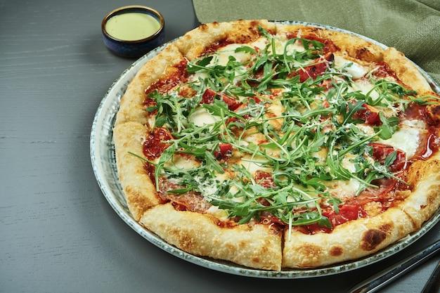 Chiuda su pizza appetitosa con il prosciutto, la rucola, i pomodori, il parmigiano e la mozzarella sulla tavola di legno in un ristorante. messa a fuoco selettiva, copia spazio