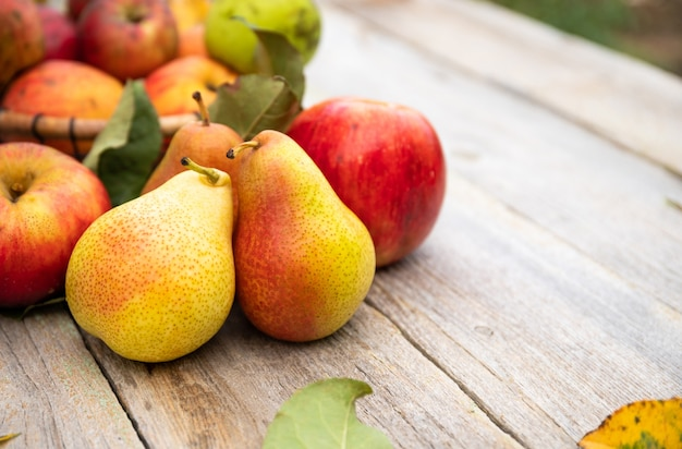 Primo piano su mele e pere sul vecchio tavolo in legno