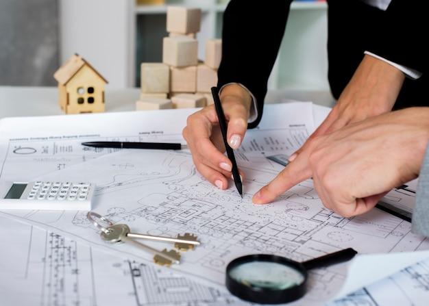 Architetti del primo piano che disegnano un progetto