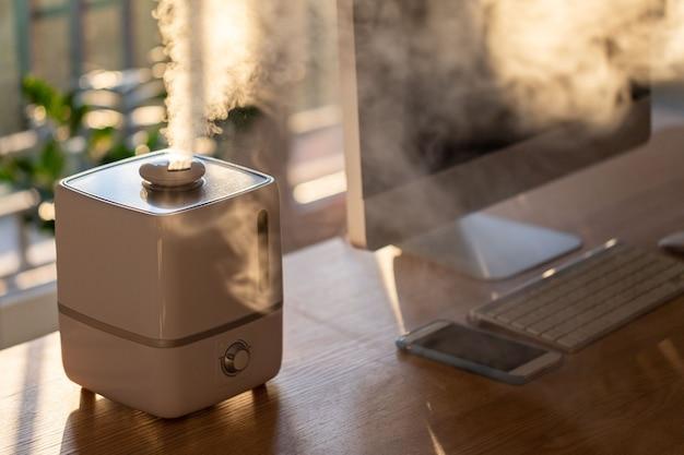 Chiuda in su del diffusore dell'olio dell'aroma sul tavolo a casa
