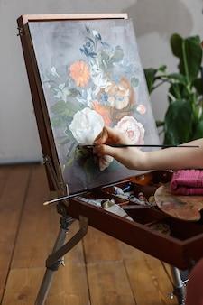 Chiuda su sulle mani dell'artista con l'immagine dei fiori della pittura della spazzola su un cavalletto