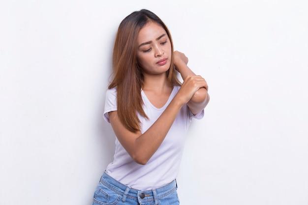 Chiuda sulla bella giovane donna asiatica che ha dolore nel gomito ferito su fondo bianco