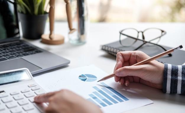 Close up donna d'affari asiatica utilizzando una calcolatrice per calcolare i numeri.finanze aziendali e concetto di contabilità