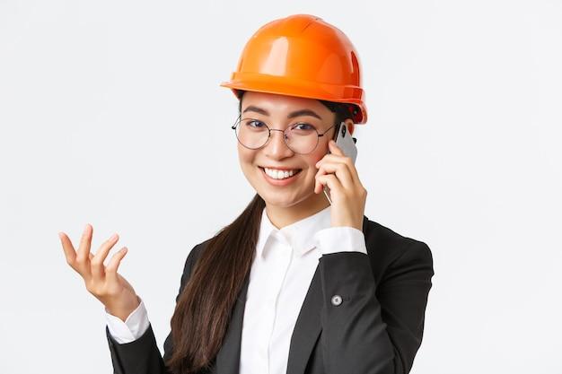 Il primo piano della donna d'affari asiatica gestisce l'impresa, l'ingegnere in casco di sicurezza e tuta ha una conversazione telefonica, chiama gli investitori, sorride mentre parla su smartphone, sfondo bianco
