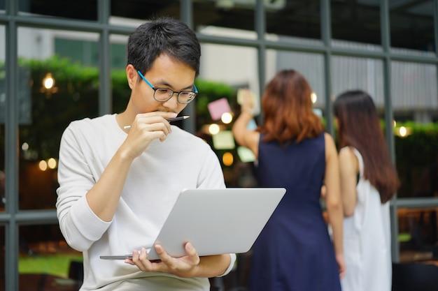 Close up asiatico creativo designer uomo pensa e lavora in ufficio con il team