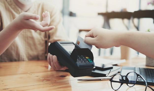 Primo piano del cliente asiatico che usa la sua carta di credito per scorrere con edc per pagare, facendo shopping con il concetto di carta di credito