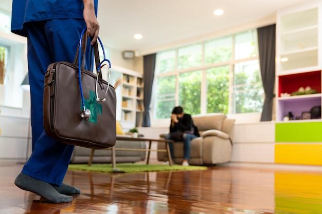 Primo piano del medico asiatico che visita un paziente a casa